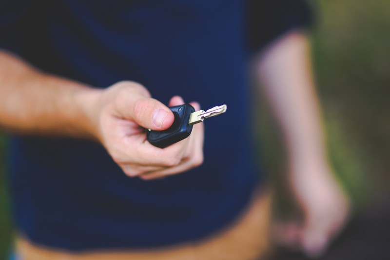 Hand holding out a car key