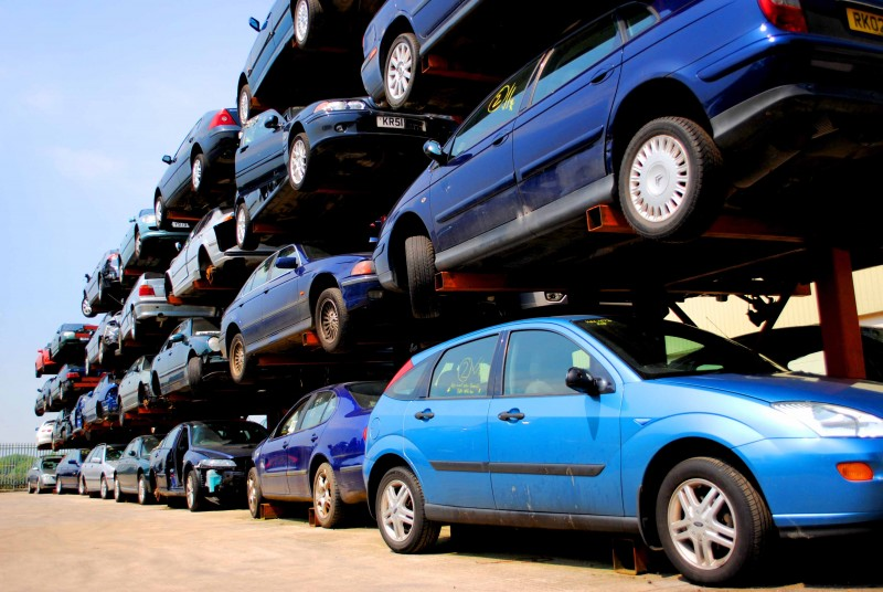 Salvaged cars stacked in racking for auction or breaking