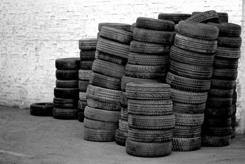 Stacks of used tyres against a wall