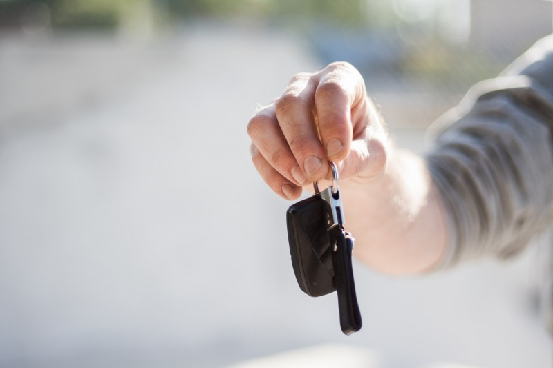 Car owner handing over keys at the end of a sale