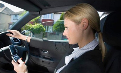 Woman texting on a phone whilst driving