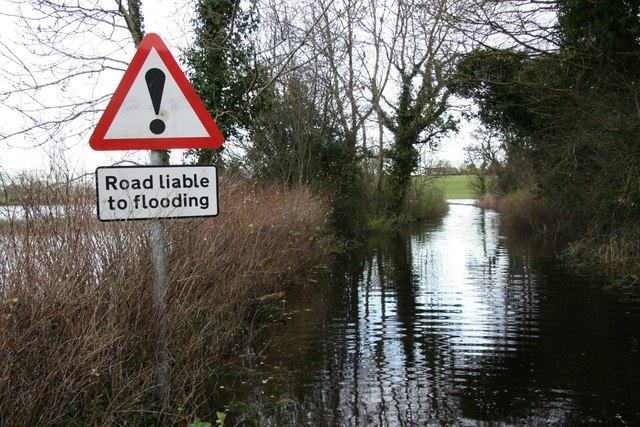 Sign says 'Road liable to flooding' adjacent a flooded road